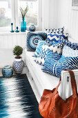 White and blue patterned scatter cushions on bench in corner against white, wood-clad walls