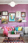 Ottoman, couch with curved backrest and colourful scatter cushions below collection of pictures on wall with purple wallpaper