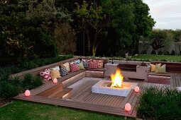 Twilight atmosphere in elegant, garden seating area in sunken wooden terrace with integrated benches and fire in central hearth