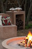 Fire in hearth and masonry benches and side table in garden