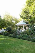 Gazebo surrounded by flowerbeds and trees seen across well-tended lawn