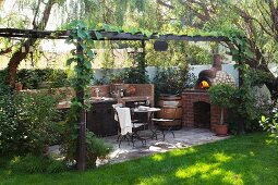 Outdoor kitchen on terrace with pergola, seating area and pizza oven in well-tended garden