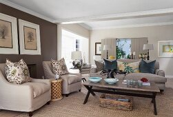 Pale armchairs with scatter cushions around coffee table in spacious living room with brown-painted accent wall
