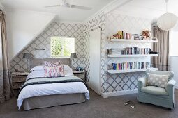 Attic bedroom with classic pattern on wallpaper, bed in corner below sloping ceiling and armchair below bookshelves