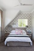 Double bed below sloping ceiling in bedroom with classic, white and grey patterned wallpaper