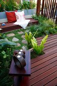 Objets d'art on side table on wooden deck; bench with cushions in background