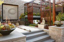 Meditation garden with bowls of succulents on walls flanking steps, Buddha artwork on stone wall and separate planted area