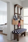 Wooden cloakroom bench with blue and white patterned cushions below accessories hung on wooden, wall-mounted rack