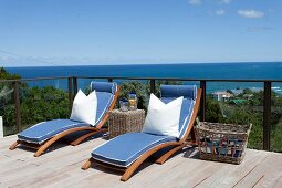 Sun loungers with blue mattresses and white pillows on wooden terrace with panoramic view of sea