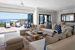 Ecru sofa set with ottoman and chaise in front of open folding door with view of sunny terrace