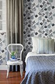 White wicker chair next to bed with patterned bedspread and wallpaper with white and blue, stylised floral pattern in bedroom