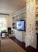 Classic fitted cabinets with large flatscreen TV and ceiling-to-floor capiz-shell lamp in foreground