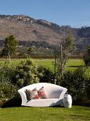 White, outdoor sofa with ethnic scatter cushions in garden in front of mountain landscape