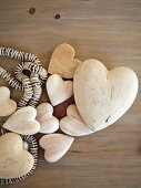 Wooden hearts of different sizes and string of beads on surface