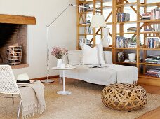 Wicker pouffe and chaise longue next to wooden partition shelving