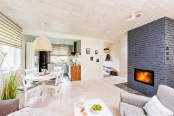 Pale, open-plan interior with fireplace built into grey brick partition and dining area below rattan pendant lamp