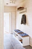 Bench with shoes and seat cushions and metal coat rack with shelf on wall in wood-panelled hallway