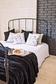 Breakfast tray on bed with dark metal frame against grey-painted brick wall partially panelled in wood