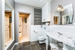 Washstand with white, turned legs on dark tiled floor against wall tiled to half height
