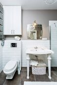 Washstand with white, turned legs against half-height tiling on wall and grey floor tiles