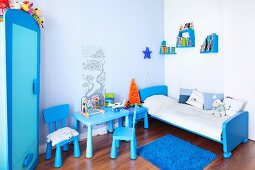 Child's bedroom in shades of blue - small chairs and table next to sleigh bed and books on staggered wall brackets