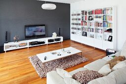 Pale sofa, coffee table on flokati-style rug, low white sideboard against dark grey wall and parquet floor