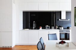 Dining area in open-plan white kitchen with black glass splashback