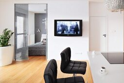 Black leather stools at a breakfast bar with a flatscreen television on the wall next to the bedroom door