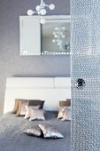 A glass door with a knob in the foreground and an unfocussed view into a bedroom with a double bed, silver decorative cushions and a grey quilt