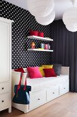 Coloured cushions on a sofa bed with drawers against a wall hung with black-and-white spotted wallpaper
