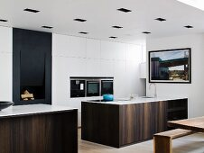 Elegant, monolithic counter with wooden front in front of white fitted cupboards with fitted appliances