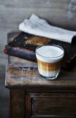 Glass of latte macchiato coffee on old cabinet