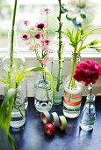 Various flowers in glass bottles decorated with masking tape on a window sill