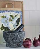 Mortar and pestle and red onions in front of collection of chopping boards