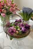 Arrangement of moss, violas and quail eggs in glass goblet, bouquet of tulips and grape hyacinths on dining table