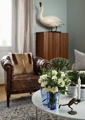 Candlestick with frog-shaped base and vase of flowers on coffee table, old leather armchair and stuffed mute swan on cabinet in background