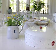 Bread bin and posy in vintage jug on dining table