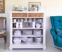 Open-fronted crockery cabinet next to swivel armchair with blue upholstery against wood-clad wall