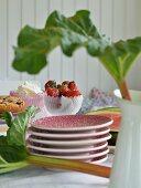 Tellerstapel zwischen Rhabarberblättern, Kuchen und Erdbeerschale auf dem Kaffeetisch