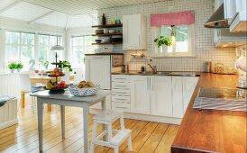 Geräumige, schwedische Wohnküche mit weißem Küchenschrank; Essplatz in wintergartenähnlichem Anbau