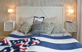 Doppelbett mit Holzkopfteil, blau-weiss gestreiftem Überwurf und gehäkelter 'Stars and Strips' Decke