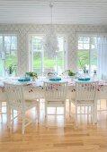 Blüten-Kronleuchter über festlich gedecktem Esstisch mit floral gemusterter Decke im weissen Esszimmer