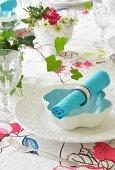 Türkisblaue Stoffserviette mit Serviettenring auf weisser Schale auf floraler Tischdecke