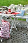 weiße Holzmöbel mit bunten Kissen und Geschirr im skandinavischen Stil auf einer Terrasse