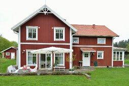 Rot-weisses, schwedisches Holzhaus mit Terrasse in grüner Landschaft