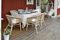 Gedeckter Tisch mit Rattansesseln und Hängesitz auf der Veranda eines Schwedenhauses
