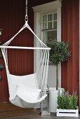 Hängestuhl neben Laterne und Olivenbäumchen auf der Veranda eines Schwedenhauses