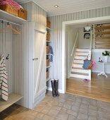 Holzverschalte Diele mit integrierter Garderobe und Blick auf zweiläufige Treppe im Hintergrund