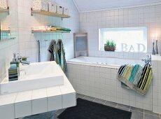 Waschtisch und Wanne in weiss gefliestem Badezimmer mit Fenster