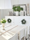 White tulips in silver goblet on rustic white table top; sideboard decorated with candles, plants & mirror in background